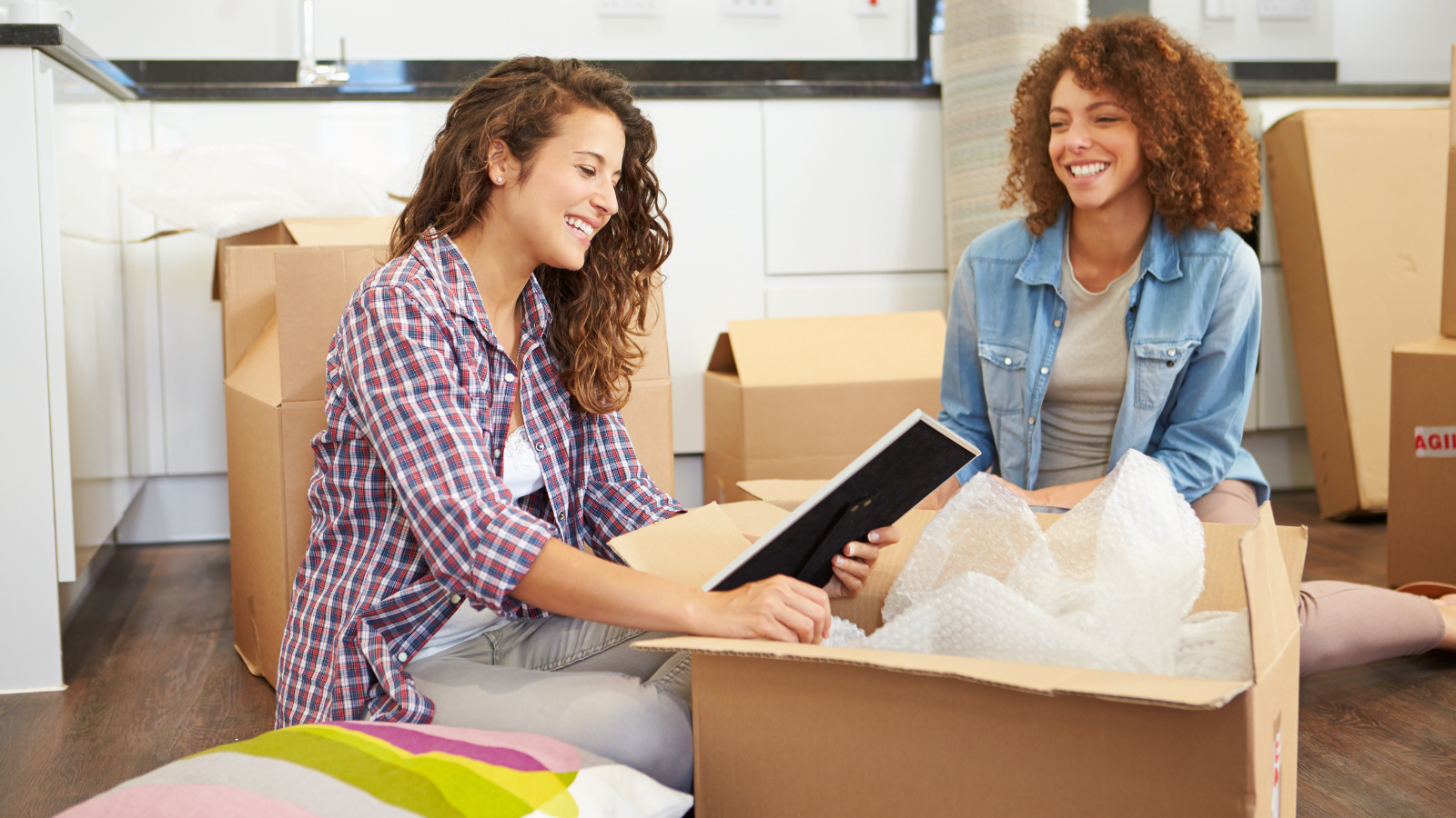 Two women sharing a laugh over some packing boxes